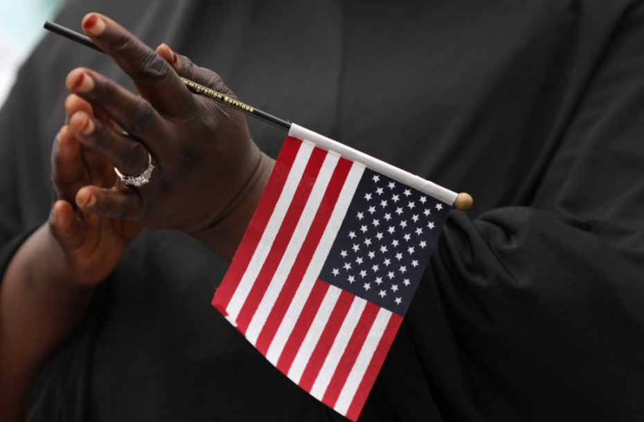 Fatoumata Jangana, from Gambia, claps holding an American flag during a naturalization ceremony at Franklin D. Roosevelt Four Freedoms Park, Roosevelt Island in New York City