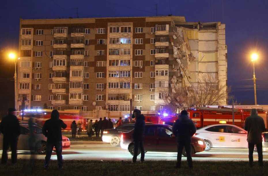 People gather near a damaged apartment block after its part collapsed in the town of Izhevsk